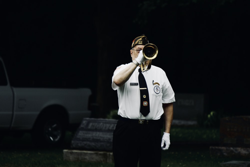 man standing and blowing trumpet