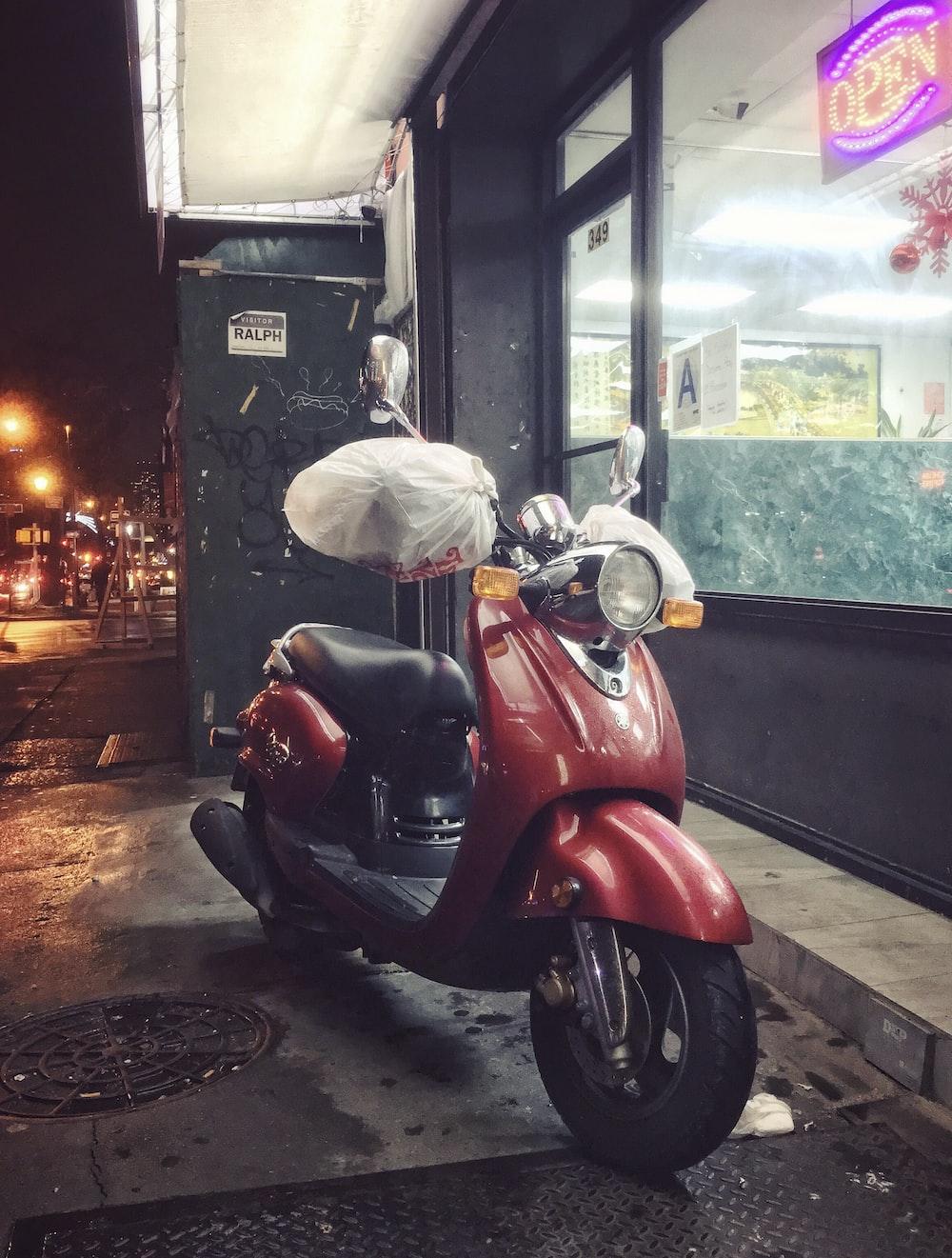 red and black motor scooter parking beside establishment