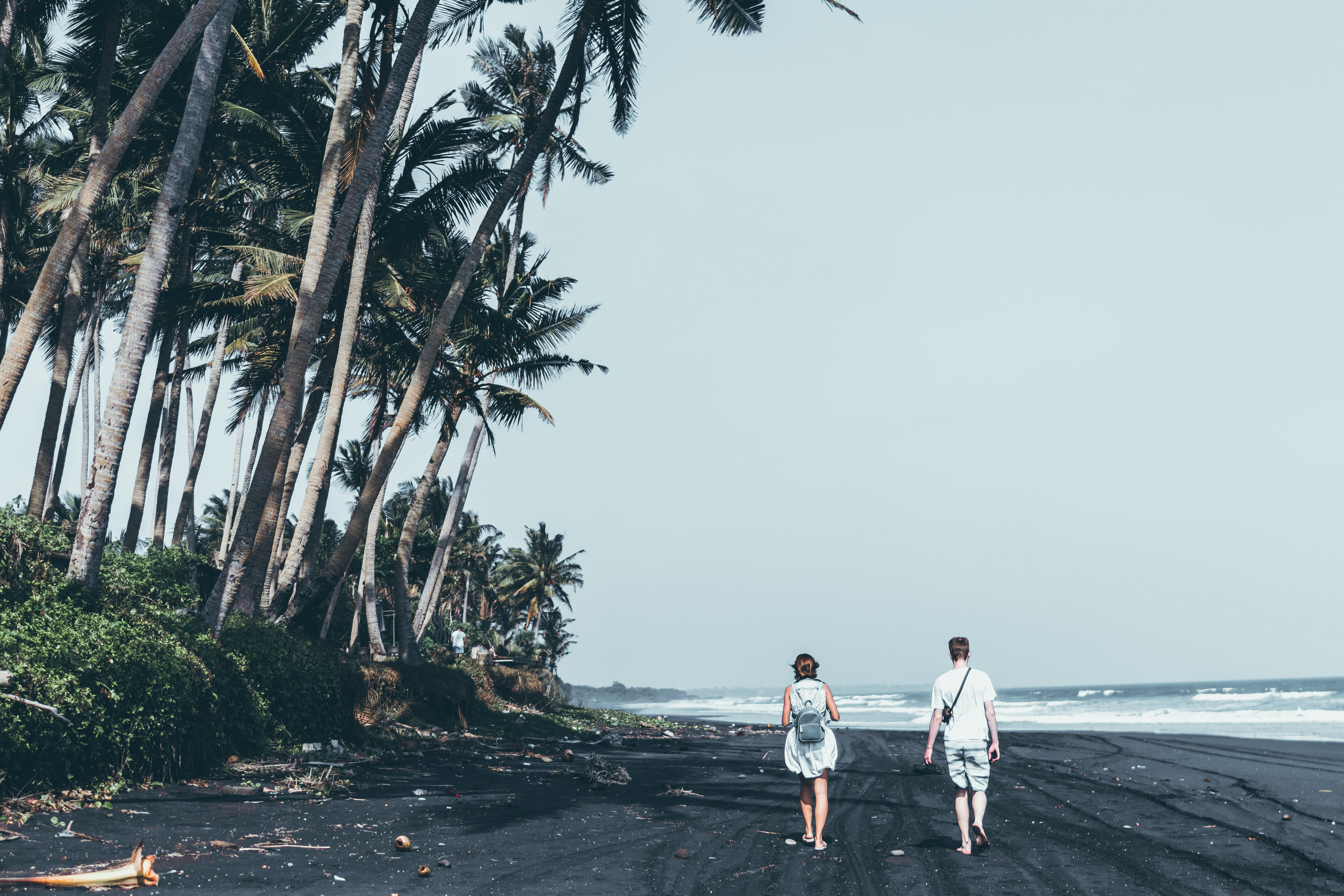 man and woman standing on the seashore