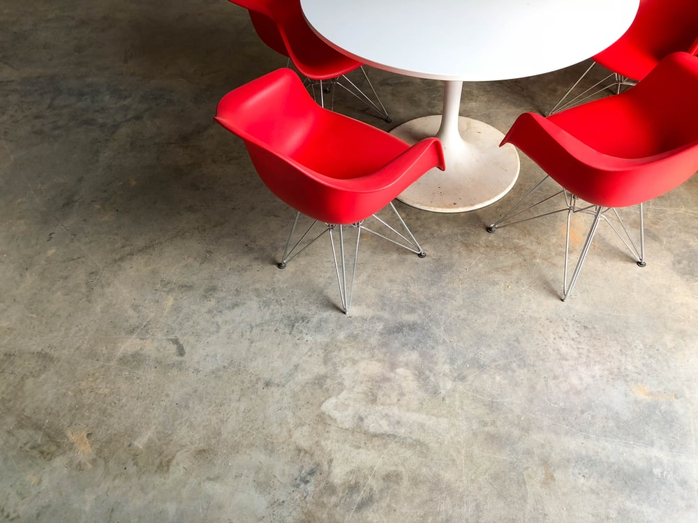 red plastic chairs near white pedestal table