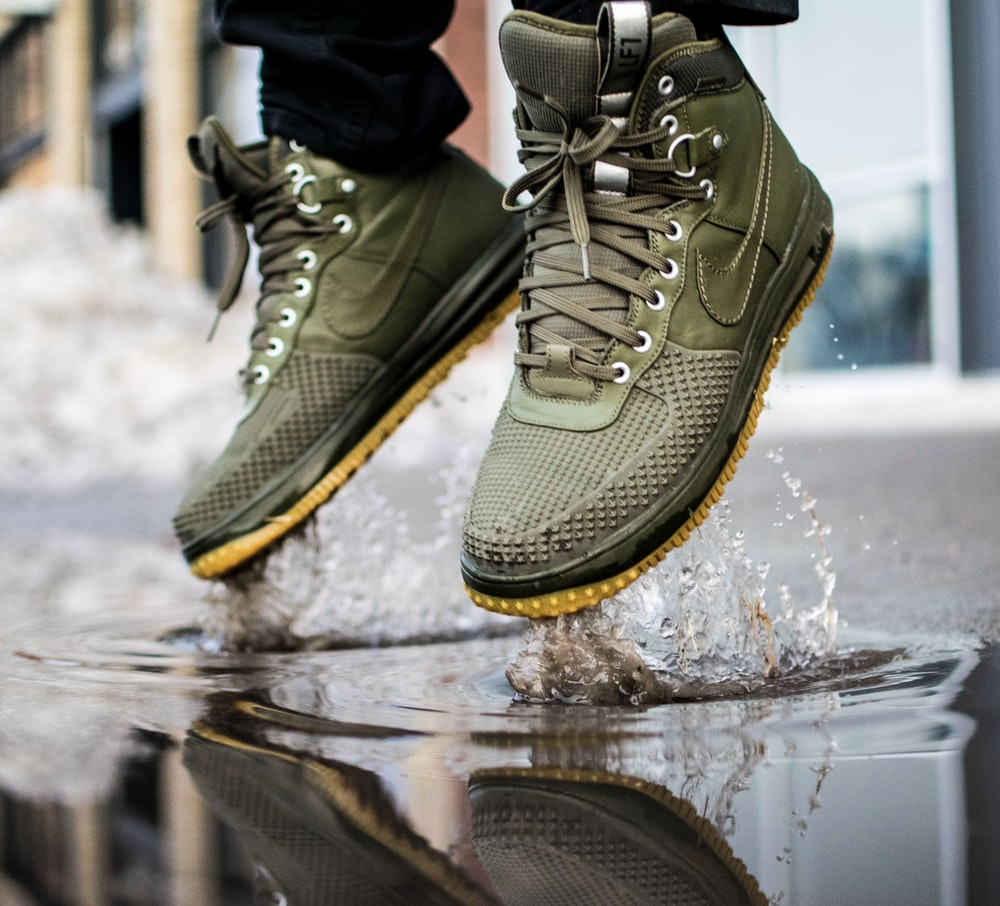 person wearing green Nike sneakers jumping on water