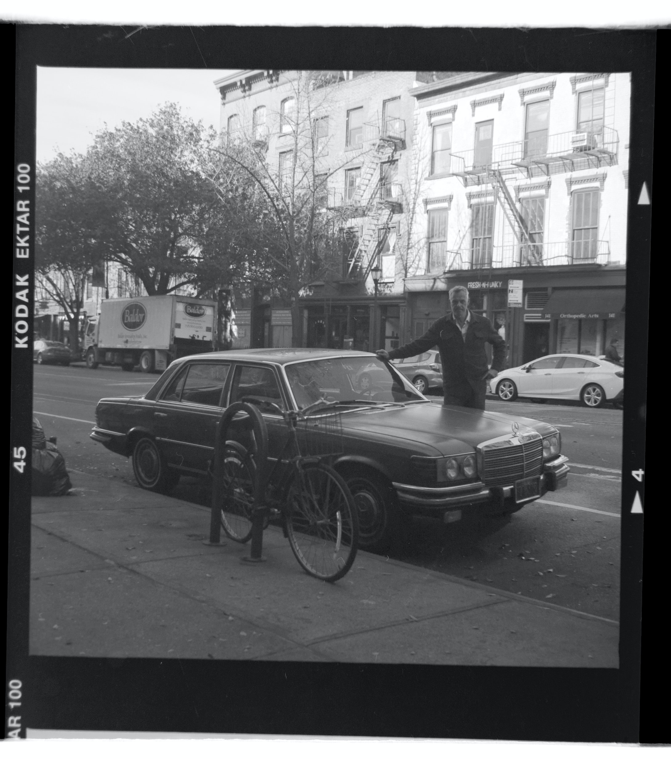 man standing on parked black car
