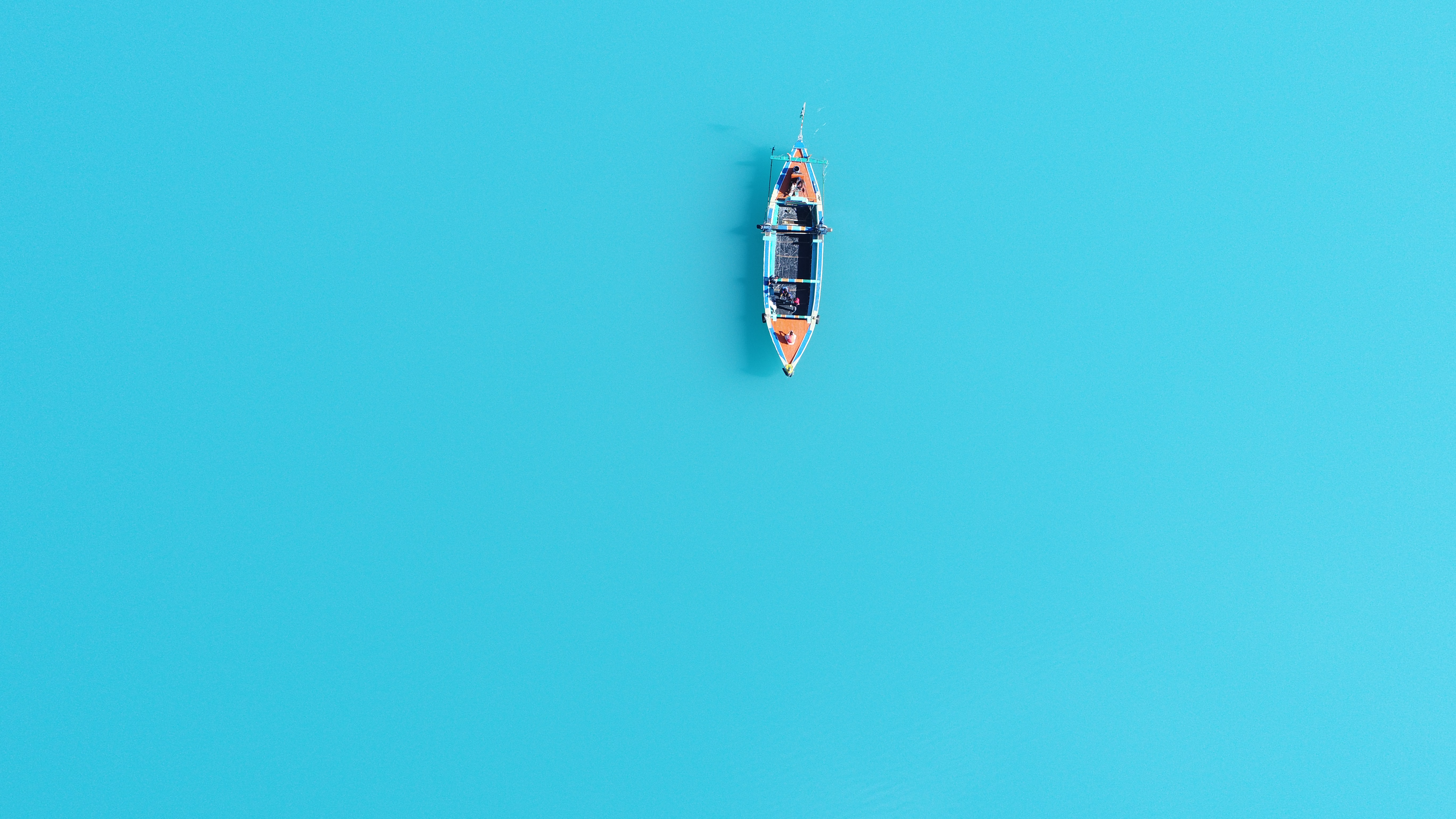 aerial photography of brown and blue canoe on body of water