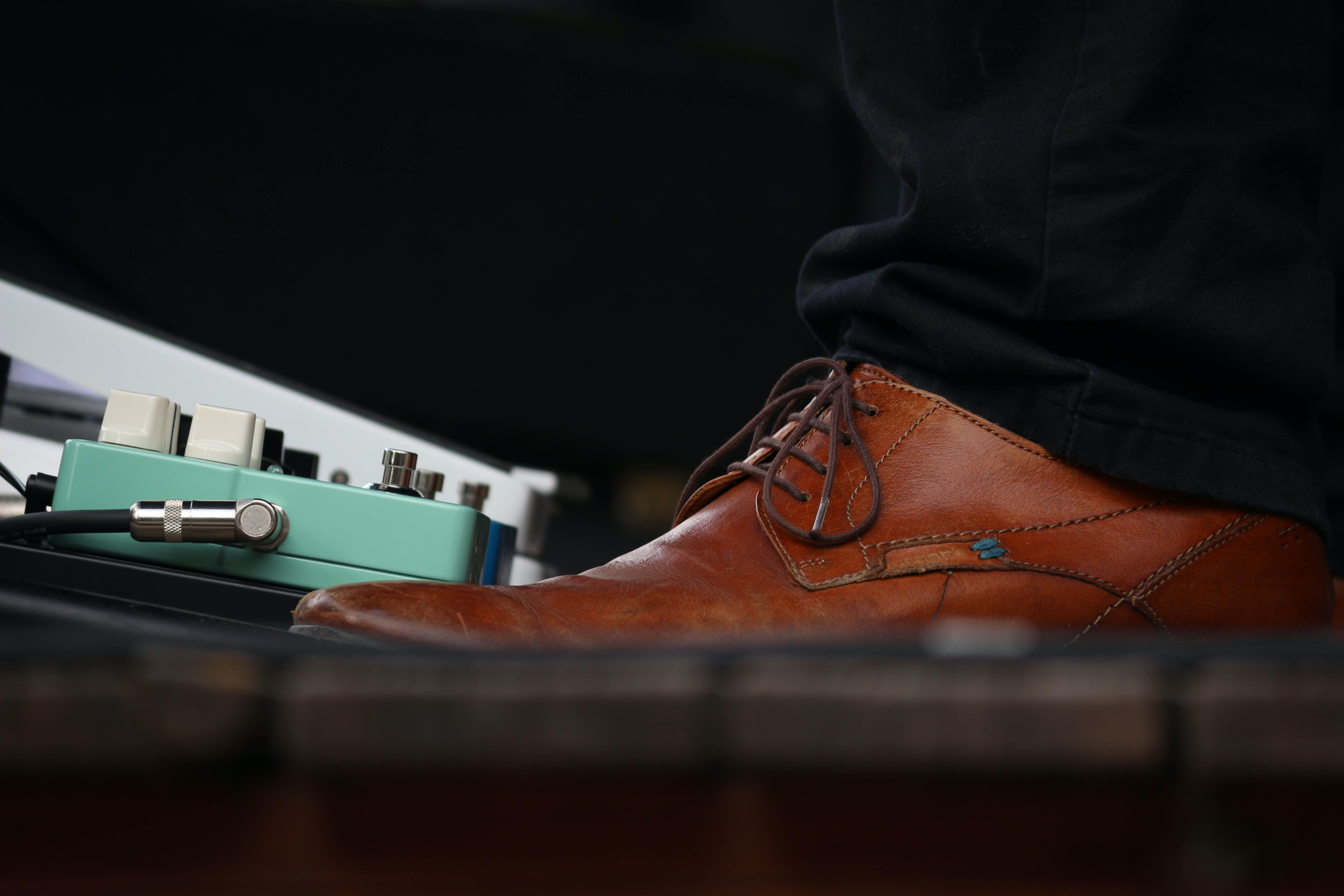 person wearing brown leather lace-up dress shoe