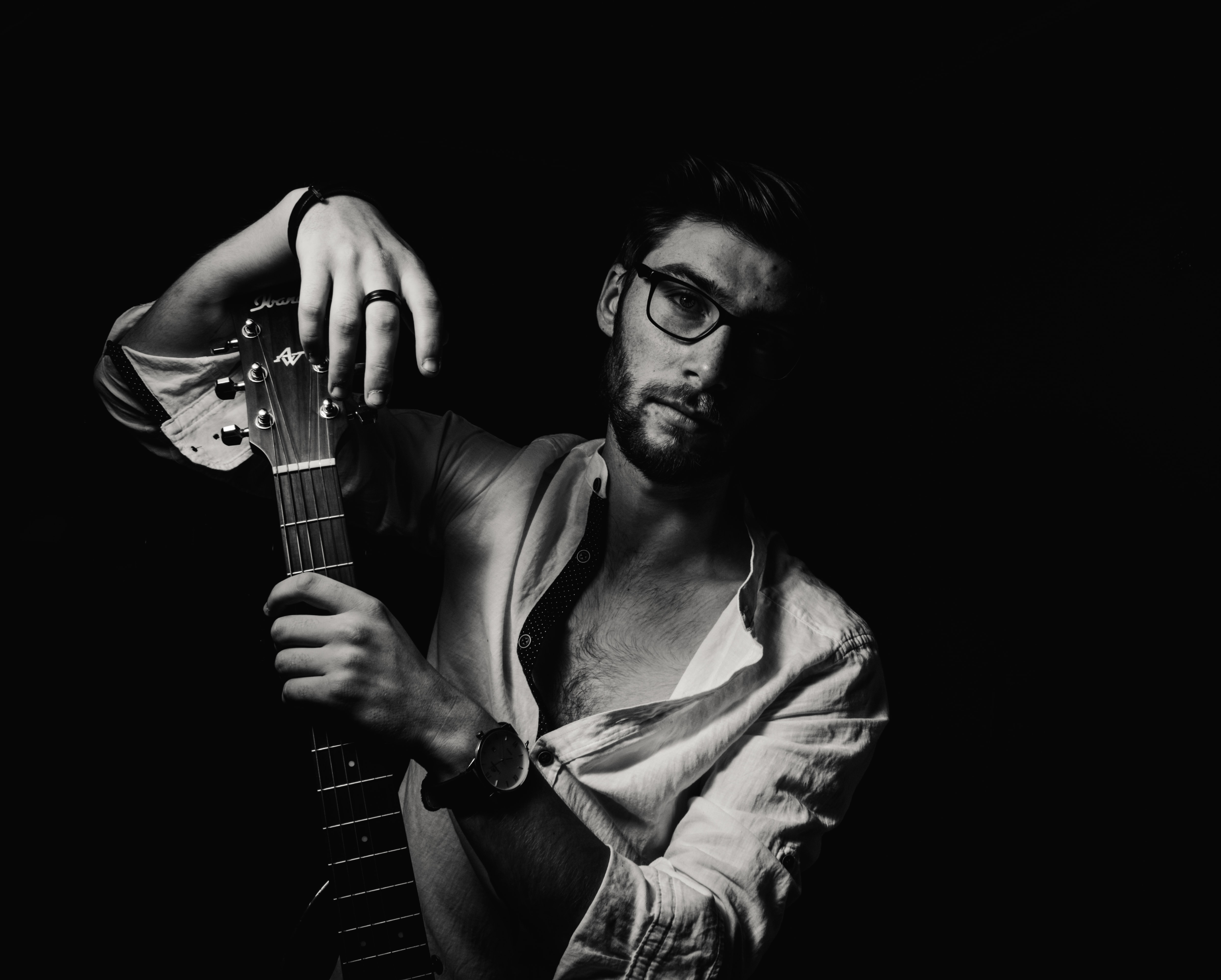 grayscale photo of man holding guitar