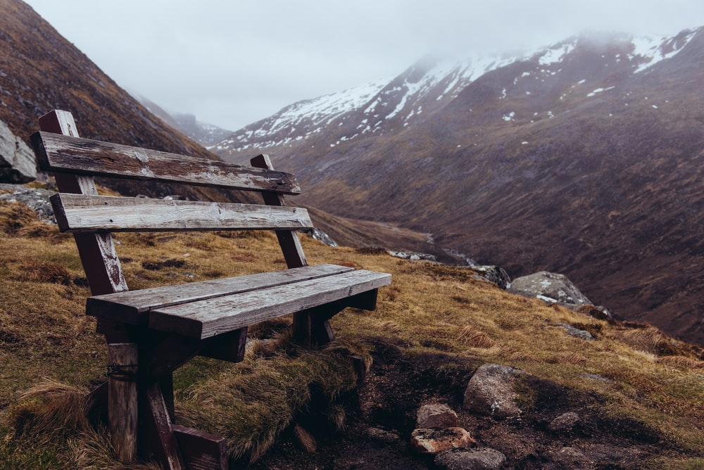 brown wooden bench on mountainside at daytime