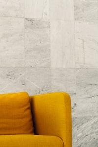 yellow sofa near gray wall