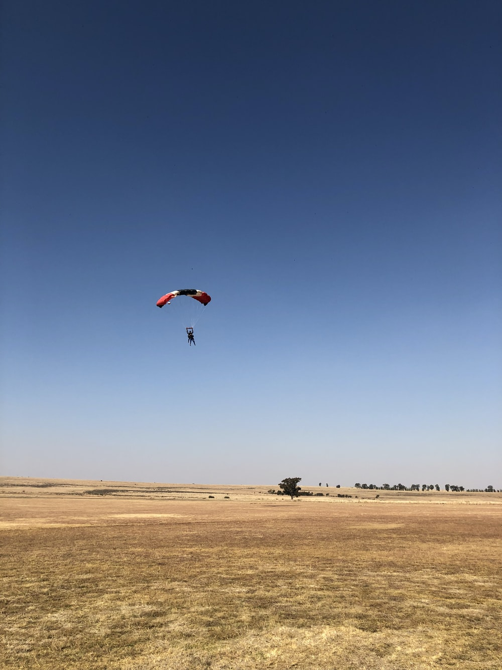 man riding on red and black parachute