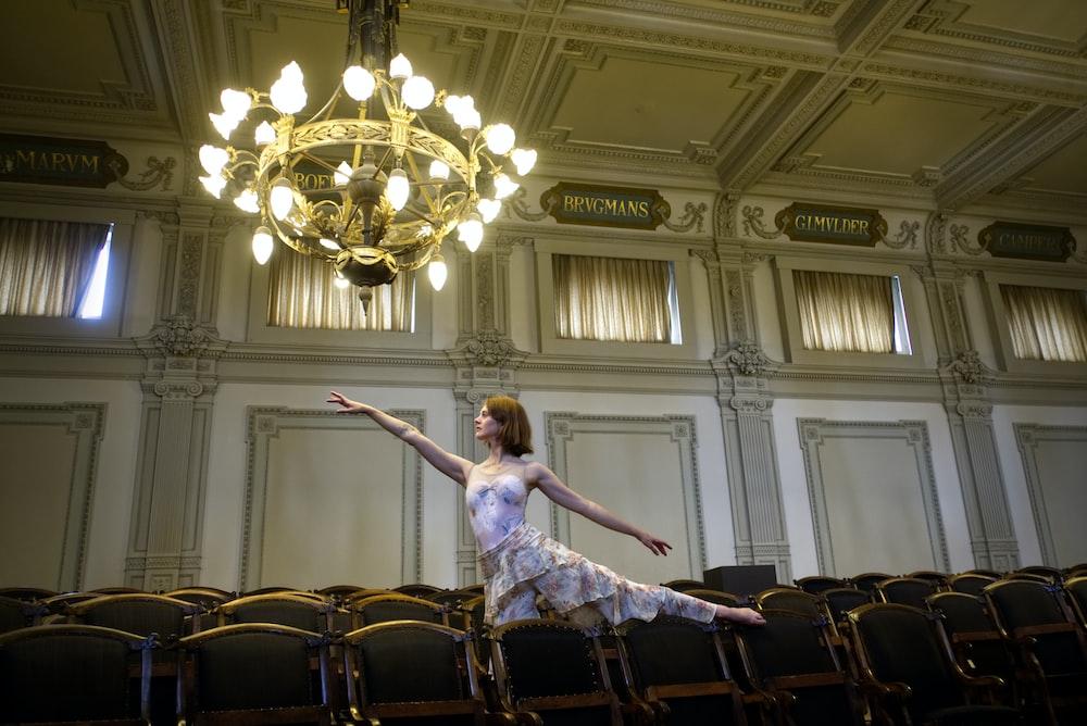 woman in pink dress dancing under of chandelier