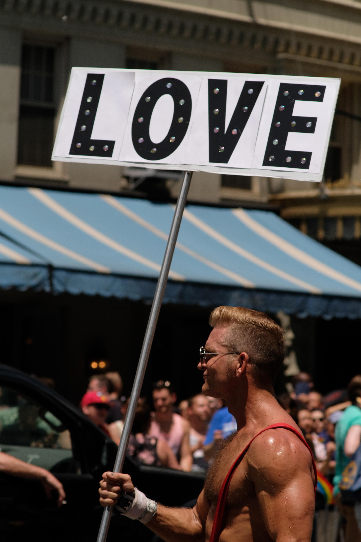 man holding love banner