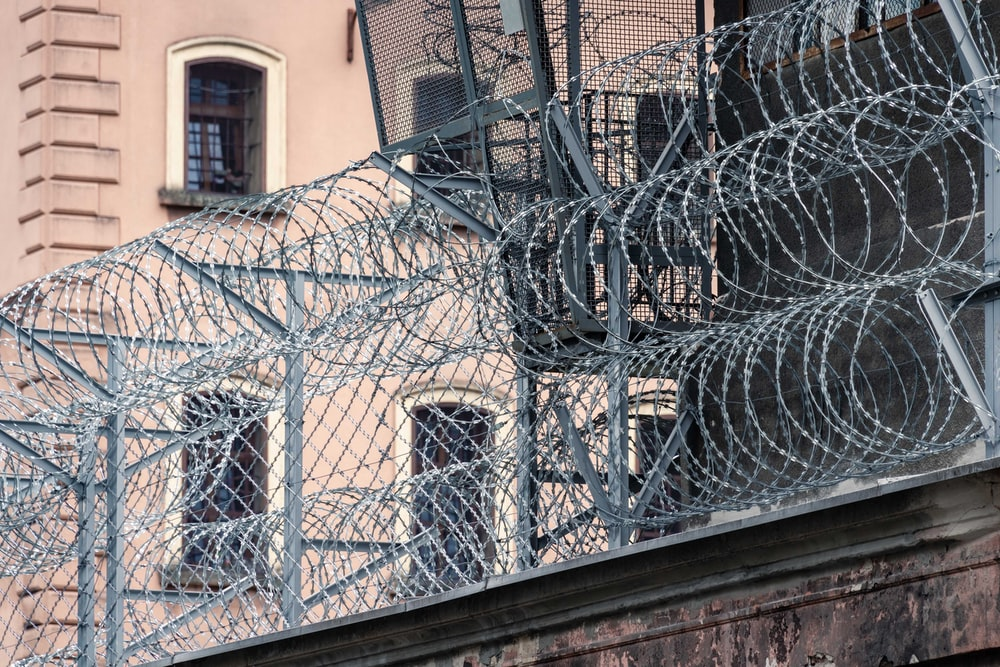gray barbwire on fence near building during day