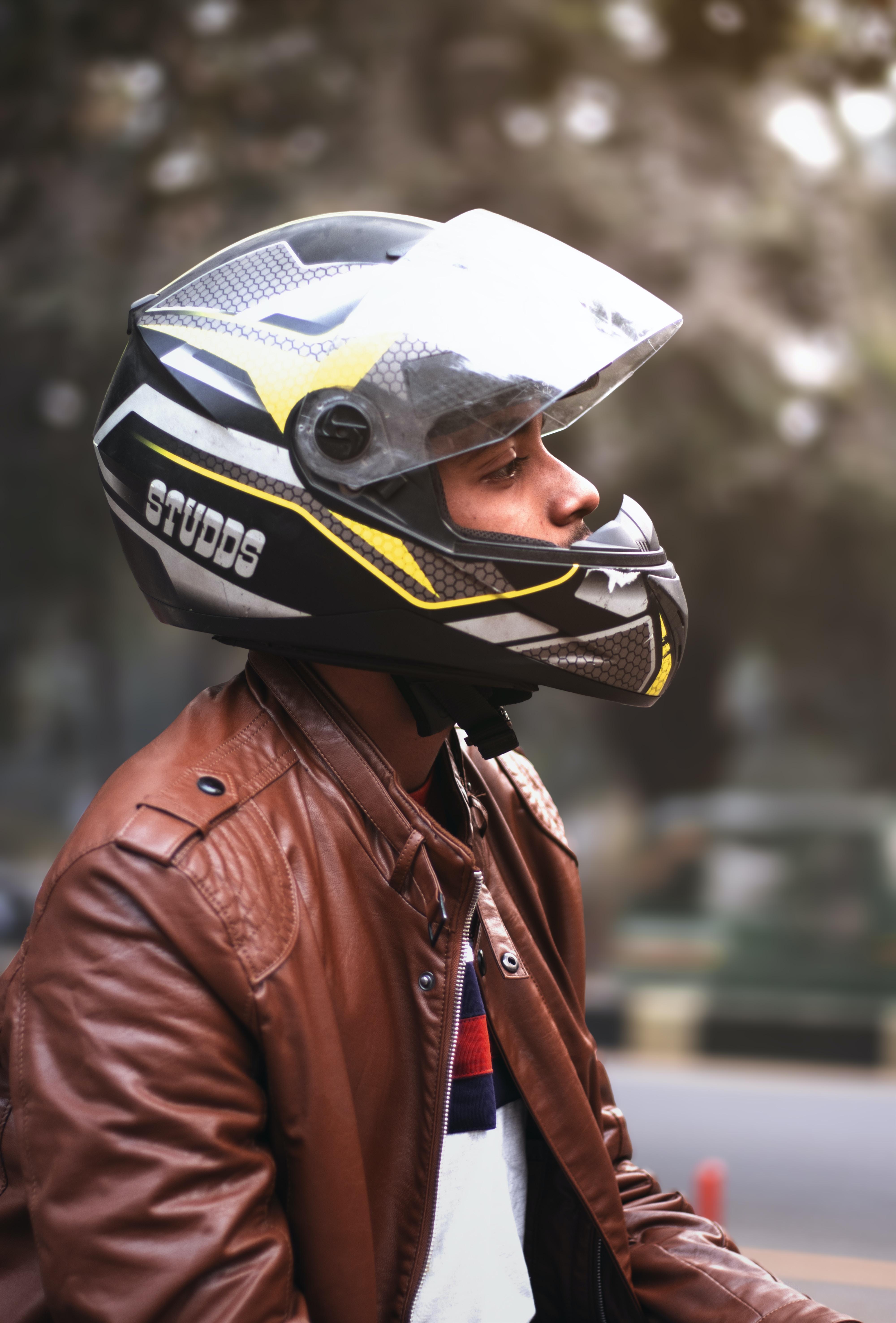 man wearing brown zip-up jacket and black full-face helmet