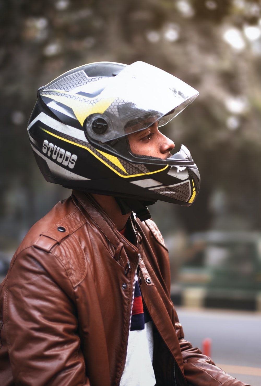 man wearing brown zip-up jacket and black full-face helmet
