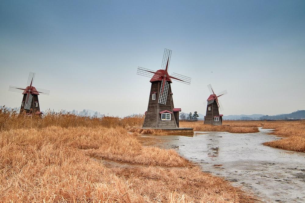 three brown windmills near river