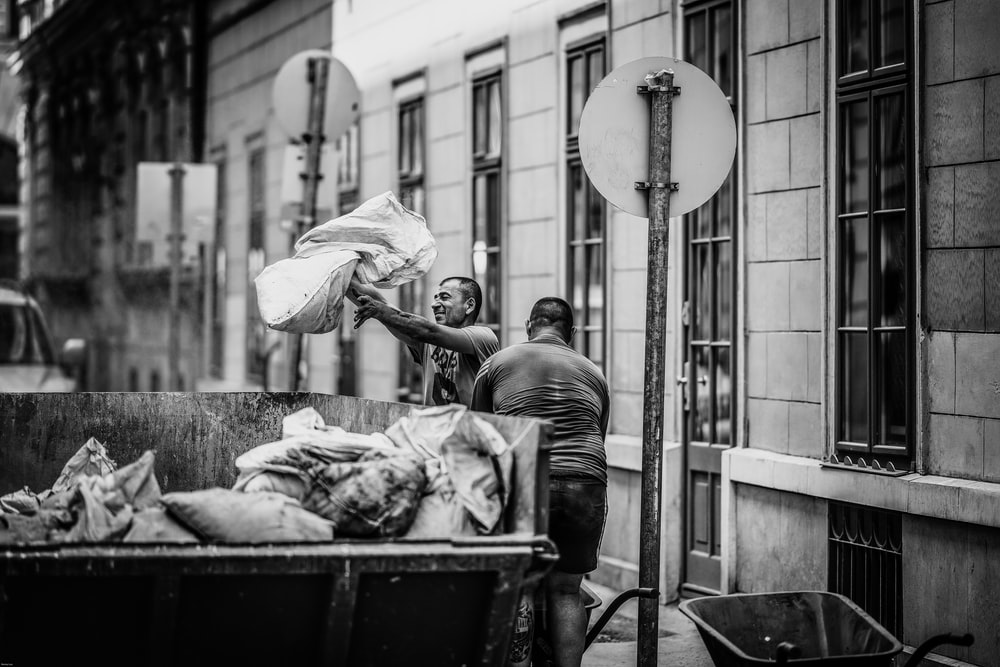 grayscale photo of two men collecting garbage