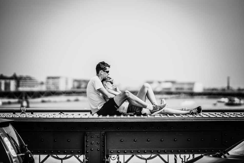 man and woman sitting on rail