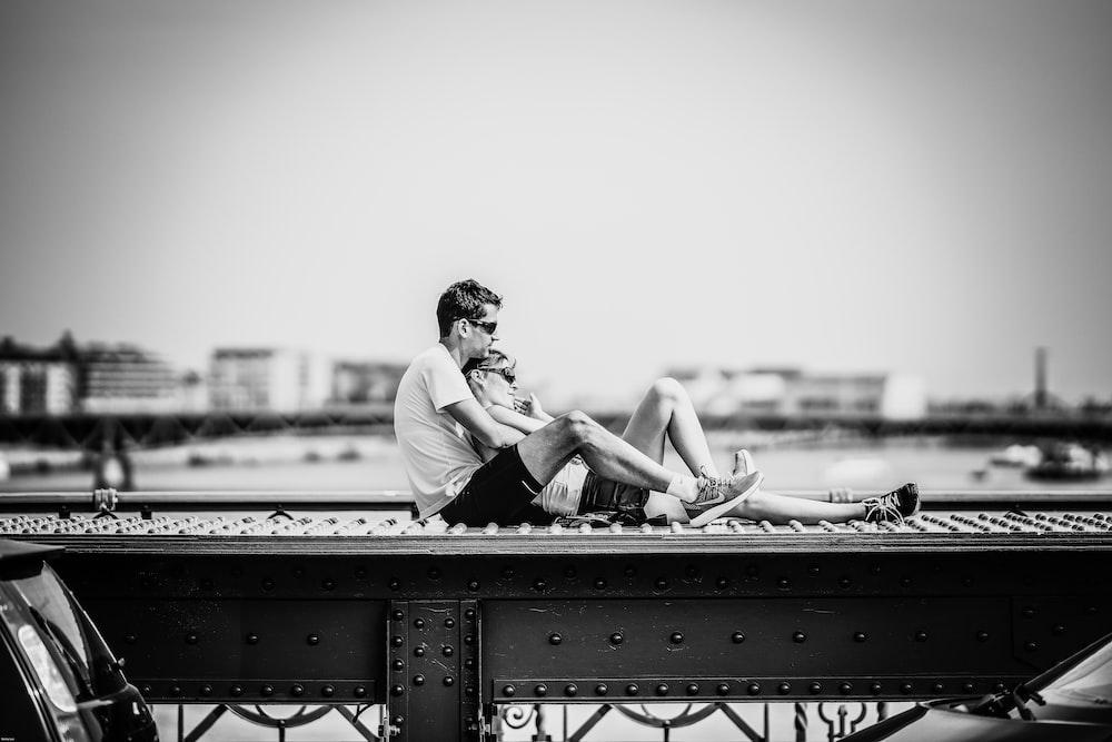 man and woman sitting on rail