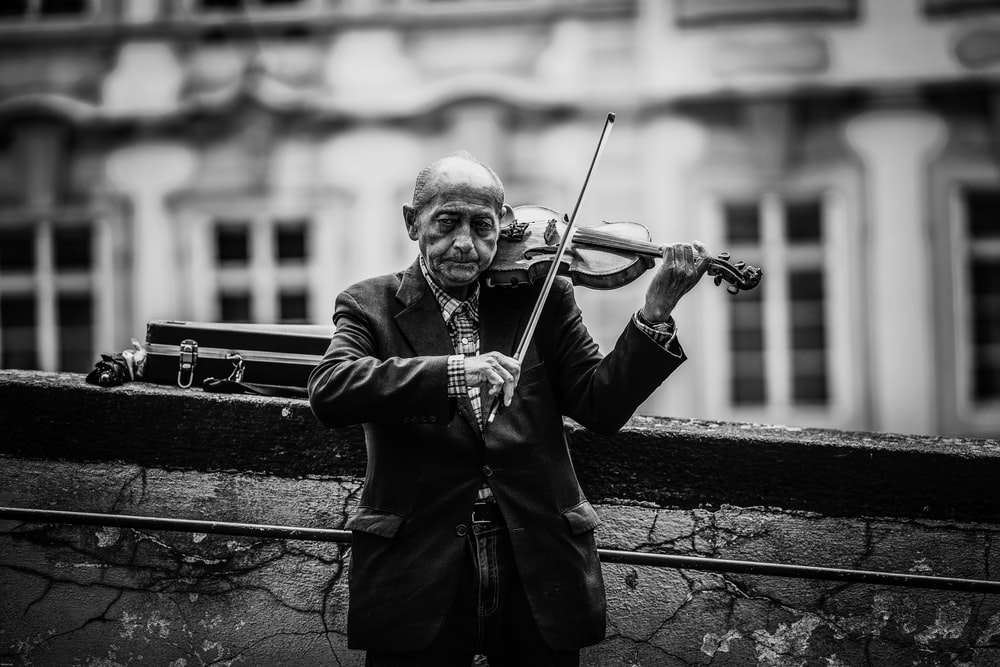 grayscale photo of a man playing vioin