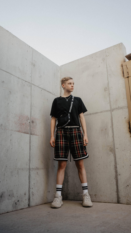 man in black shirt standing beside grey wall