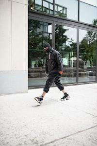 man in black hoodie walking on street