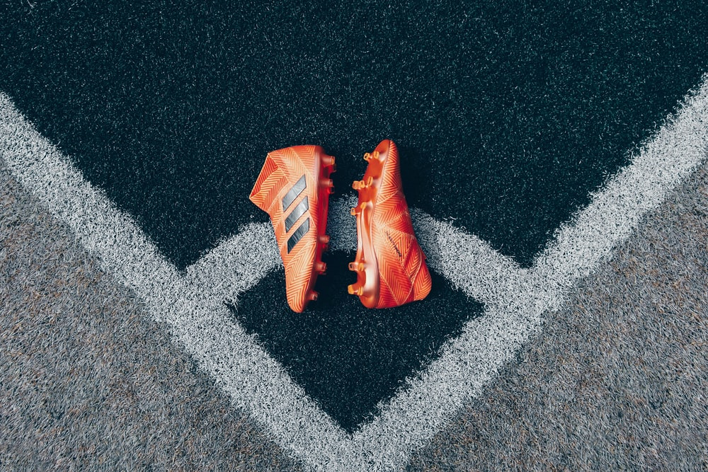 pair of orange adidas cleats on gray surface