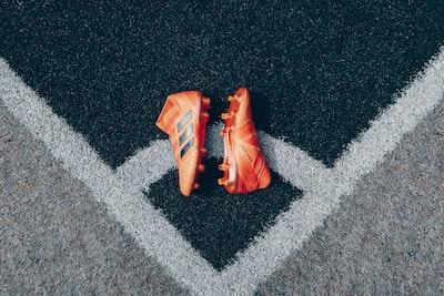 pair of orange adidas cleats