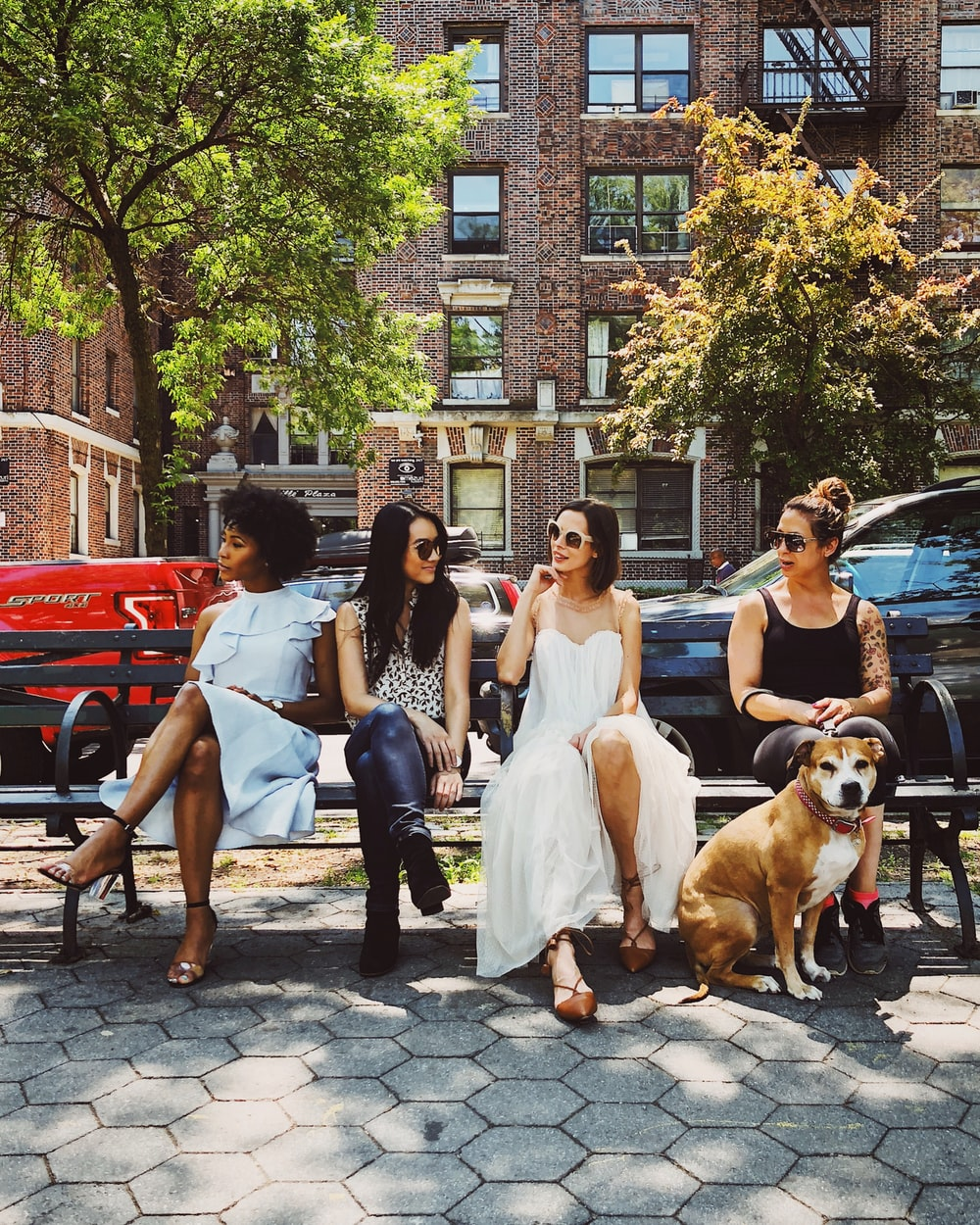 four women sitting on black steel bench during daytime