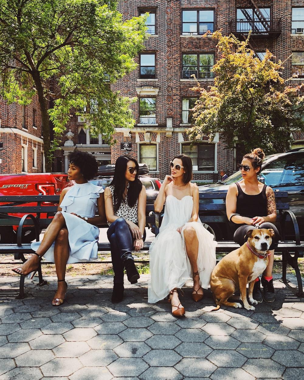 four women sitting on black steel bench during daytime