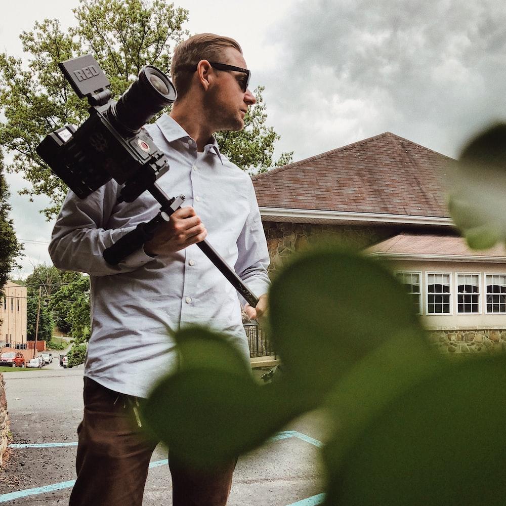 man in gray dress shirt holding camera