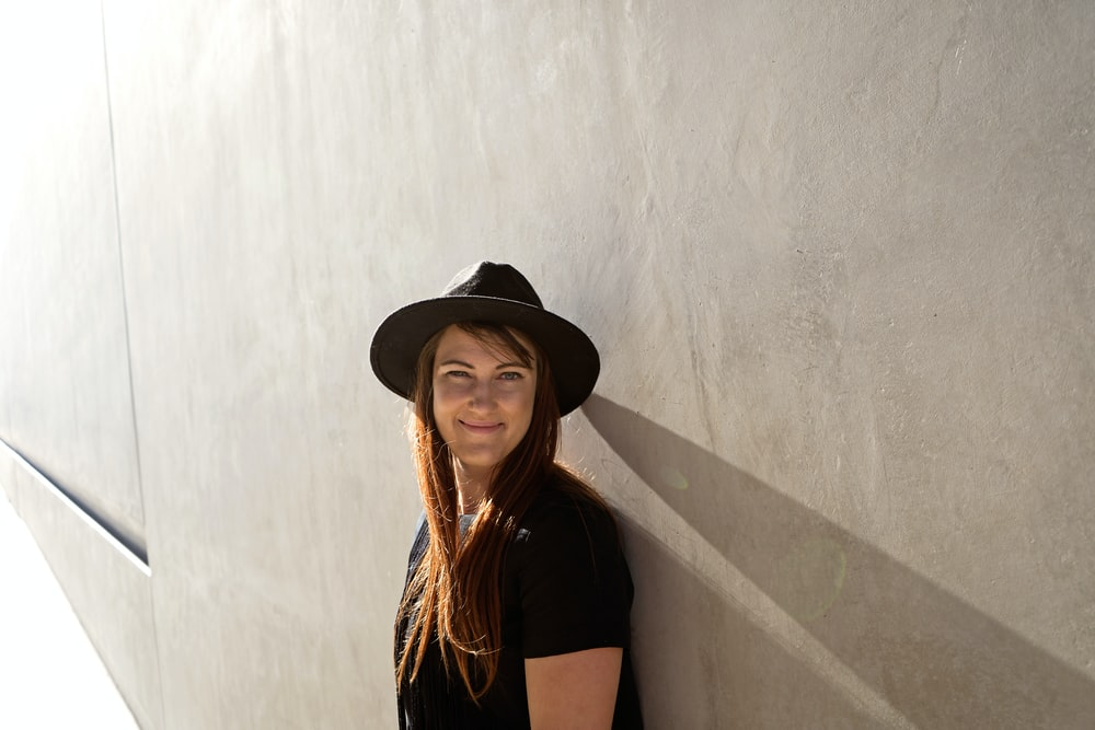 woman leaning on gray concrete wall