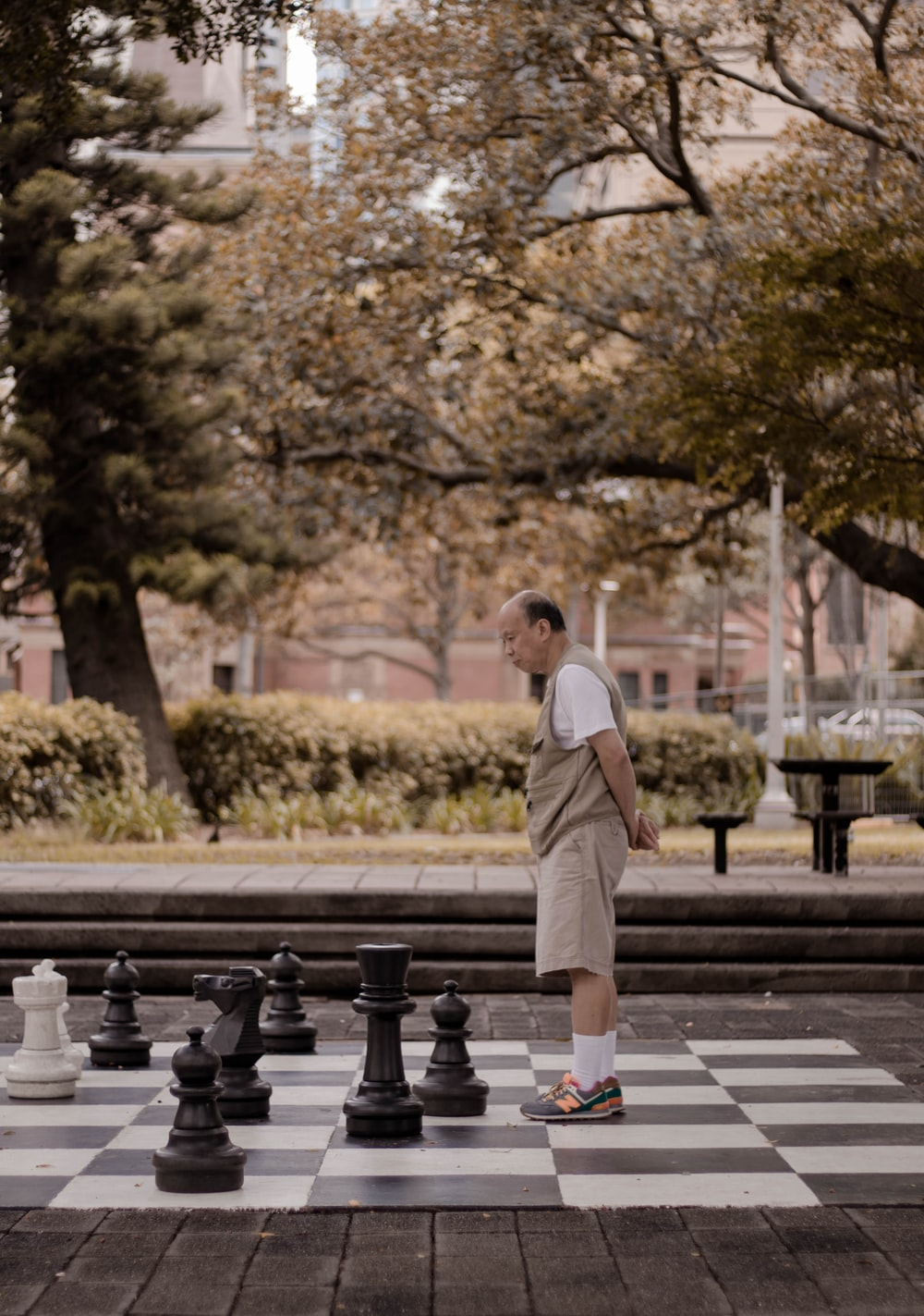 man standing on big chessboard with chest pieces at park