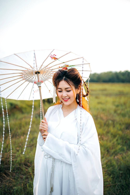 woman wearing white kimono dress and holding white umbrella