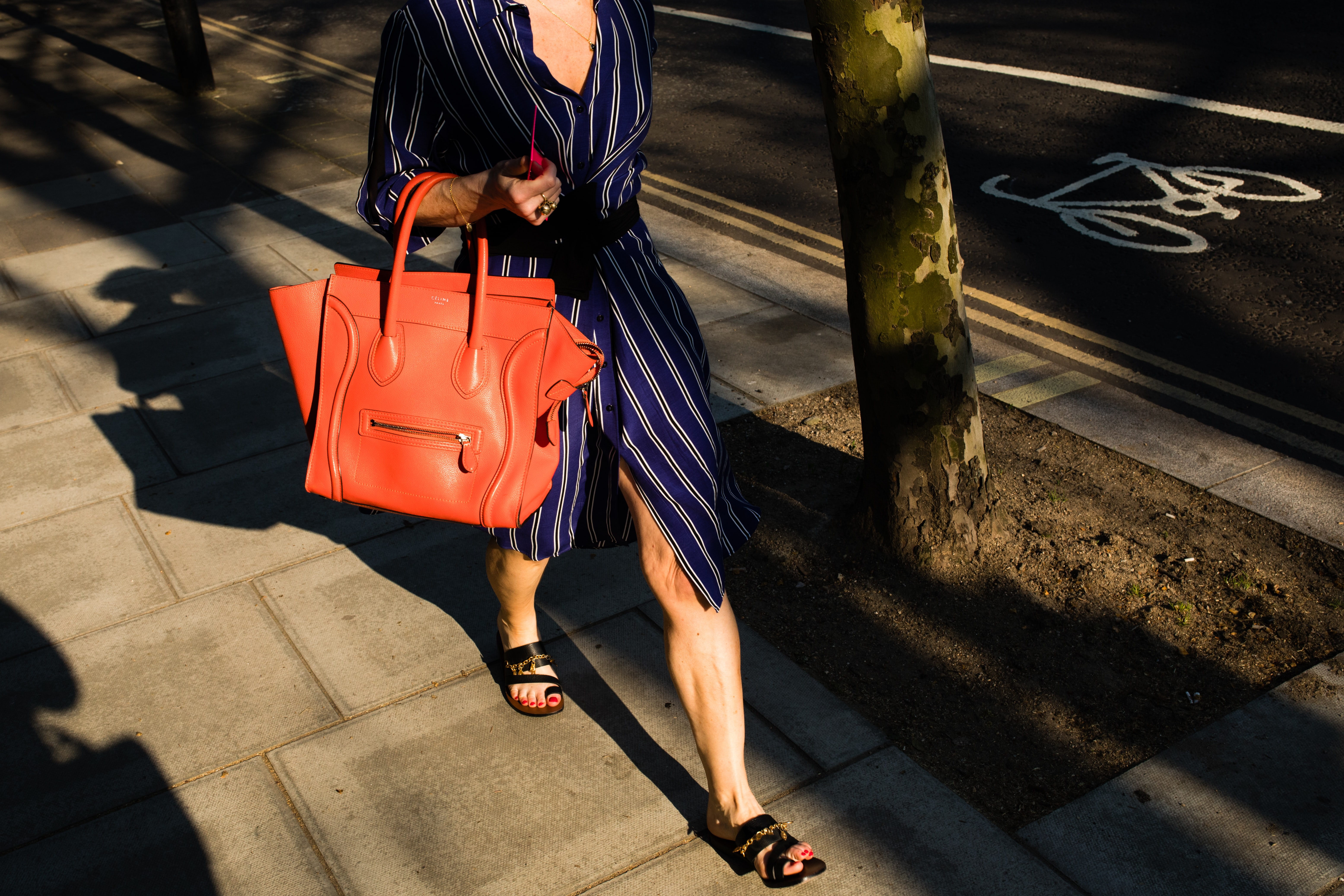 woman wearing blue dress with orange leather bag walking at the sidewalk