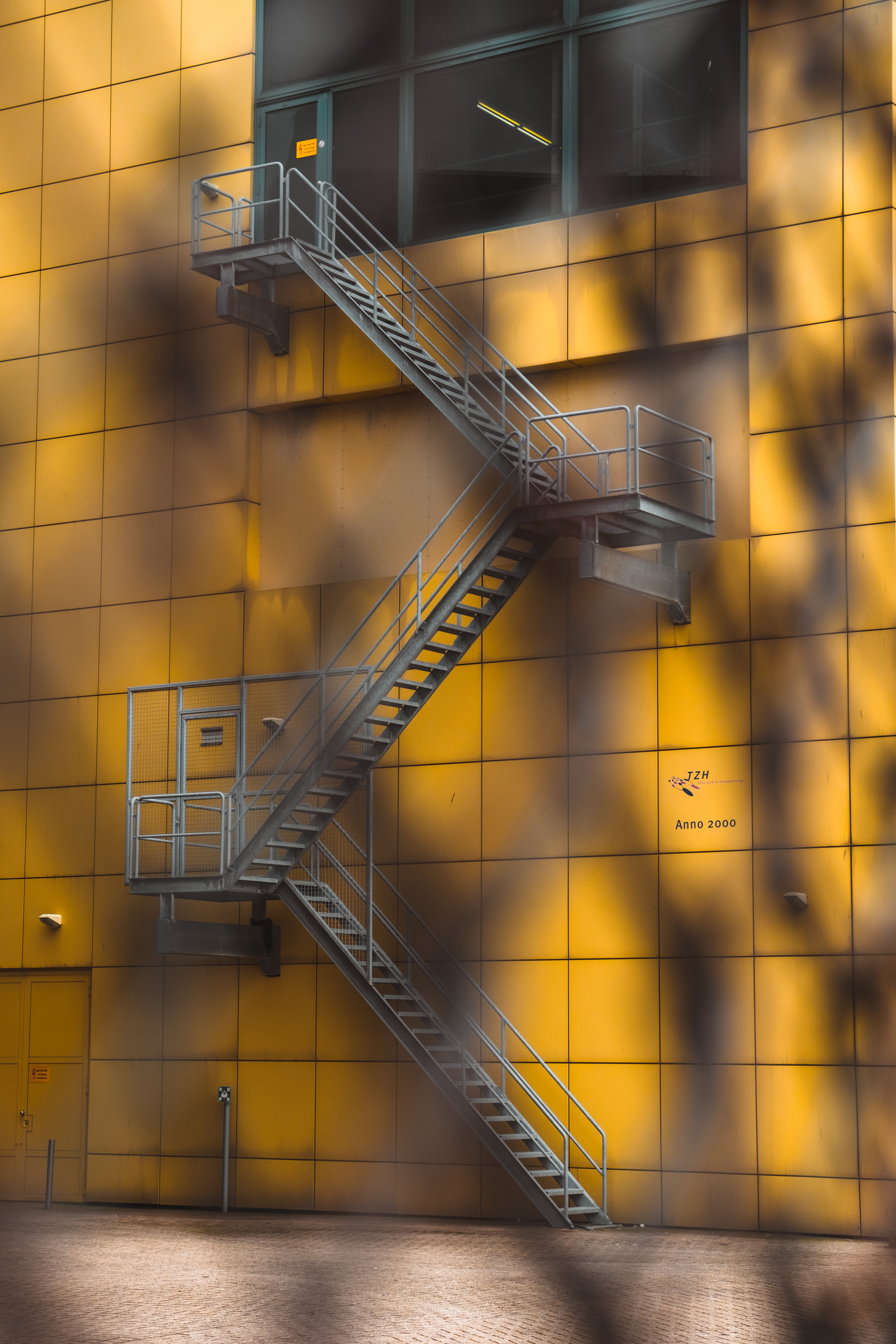 gray steel ladder beside yellow building