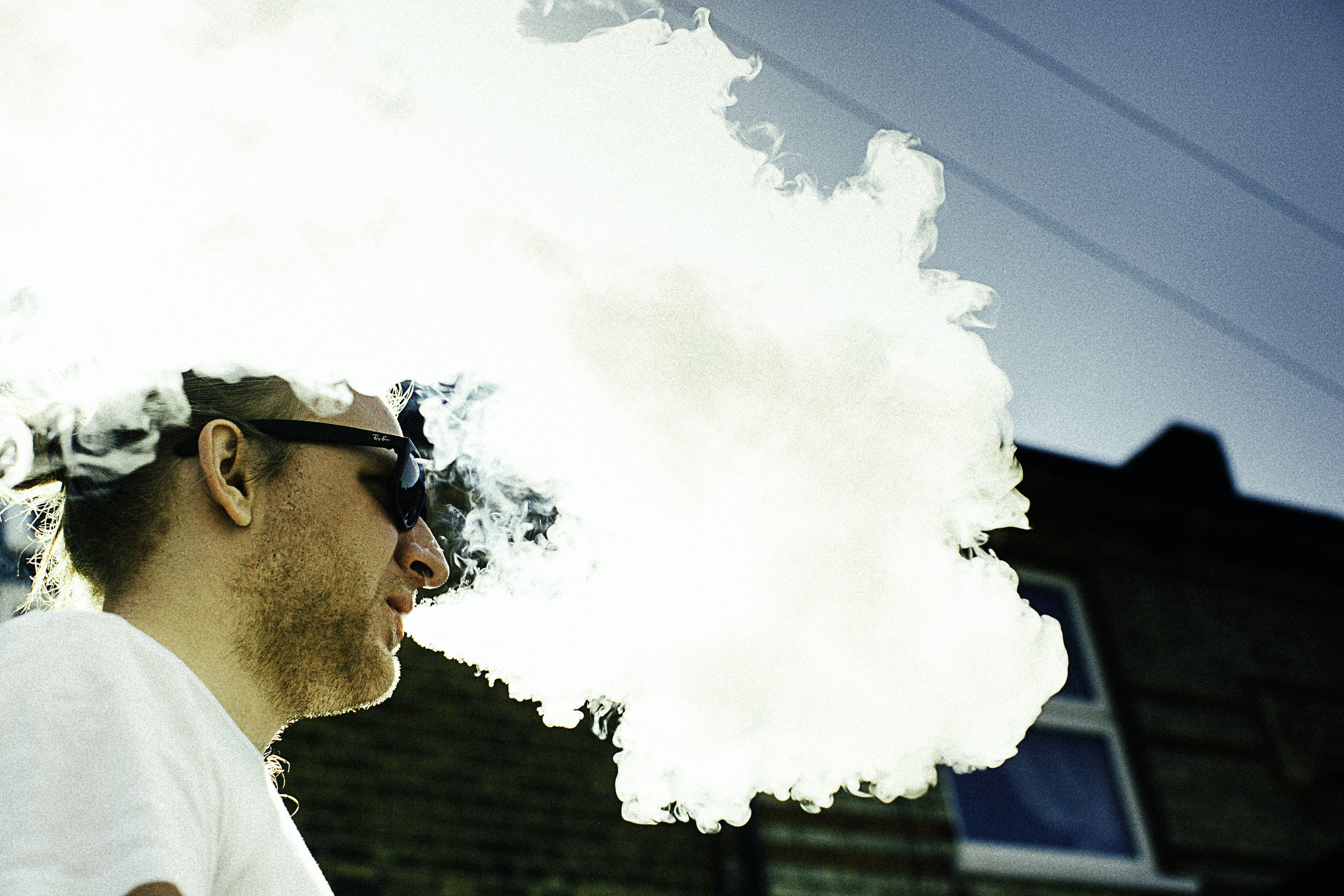 man blowing thick white smoke on air overlooking black building wall at daytime
