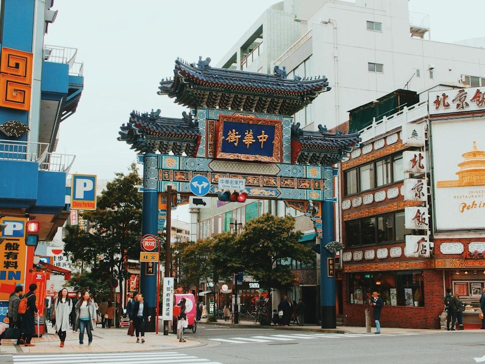 people walking pass blue Chinese gate
