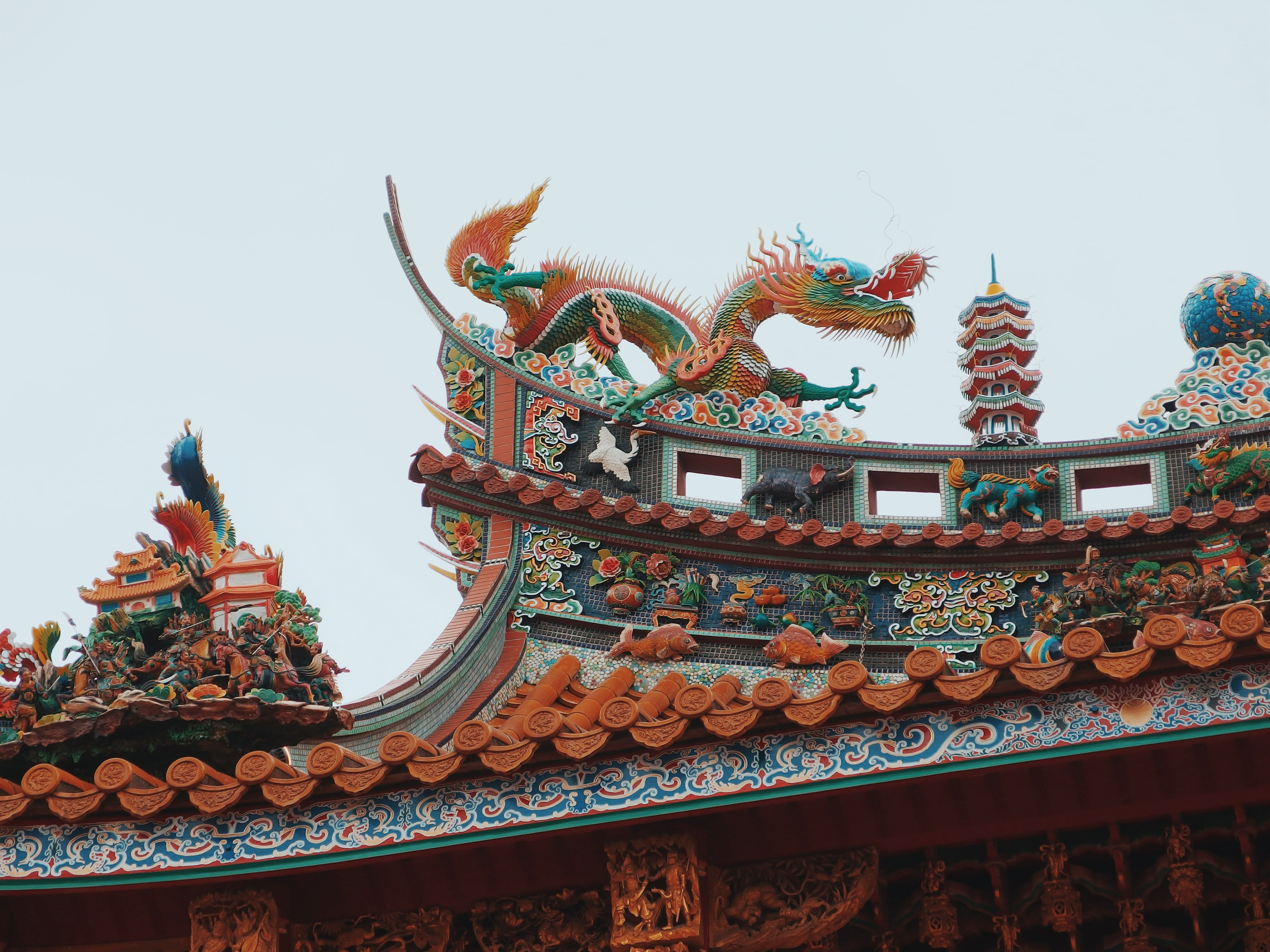 person taking photo of green and orange dragon temple