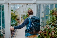 man in blue denim jacket and black hiking backpack stands on door near green plants