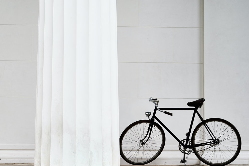black bicycle standing on white concrete building