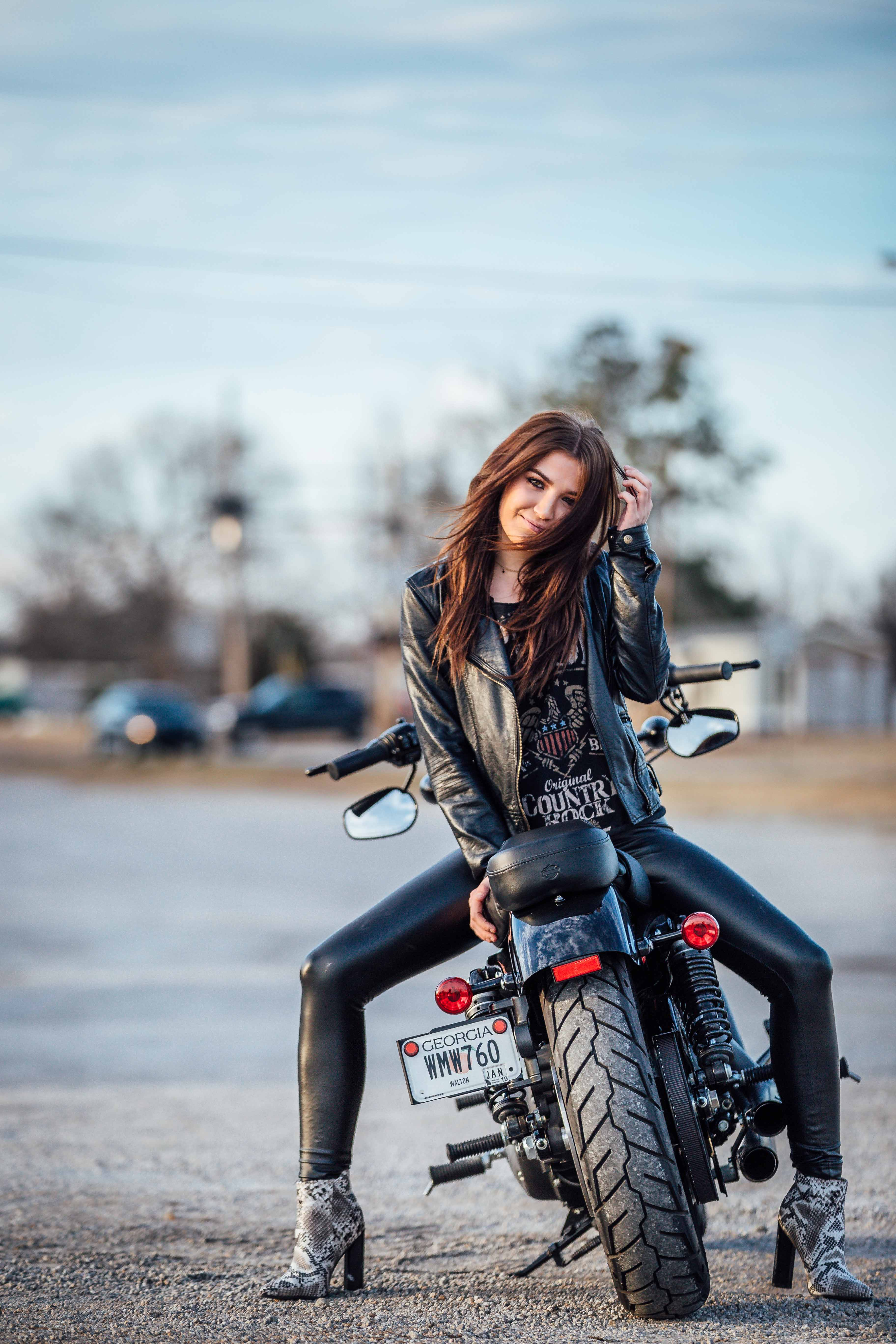woman in gray jacket sitting on motorcycle