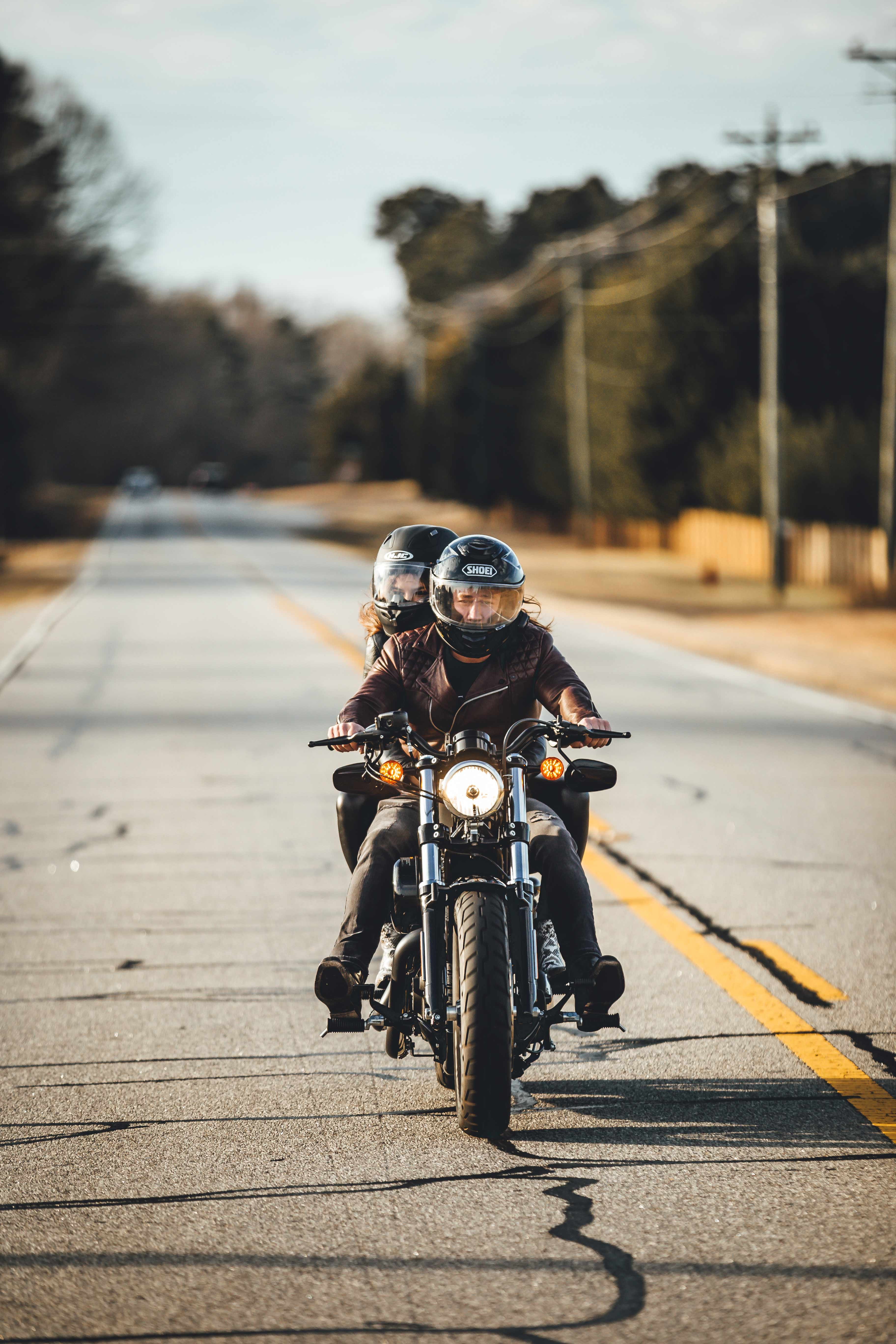 two person riding black touring motorcycle on asphalt road at daytime