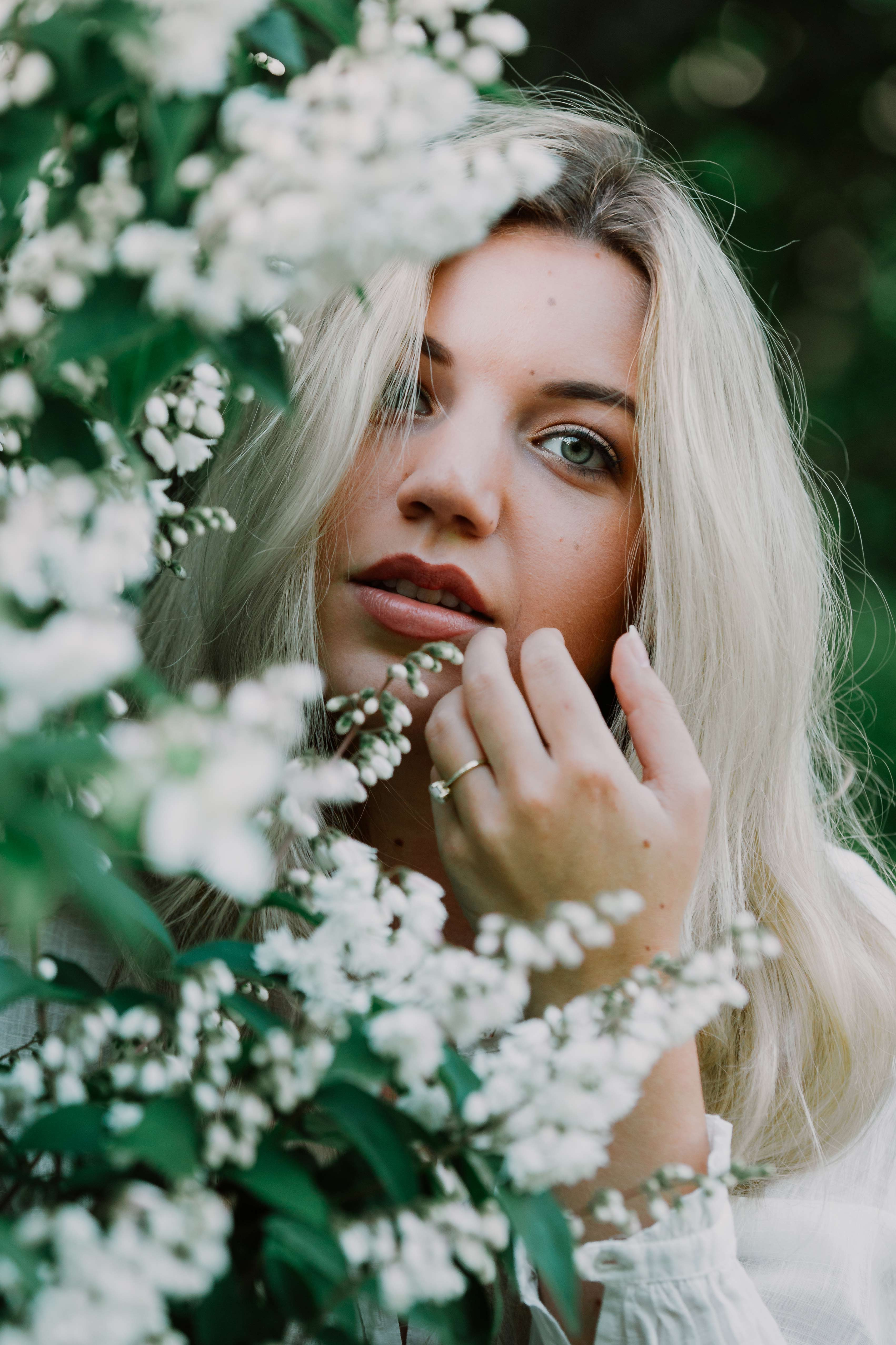 selective focus photography of woman beside white flowers