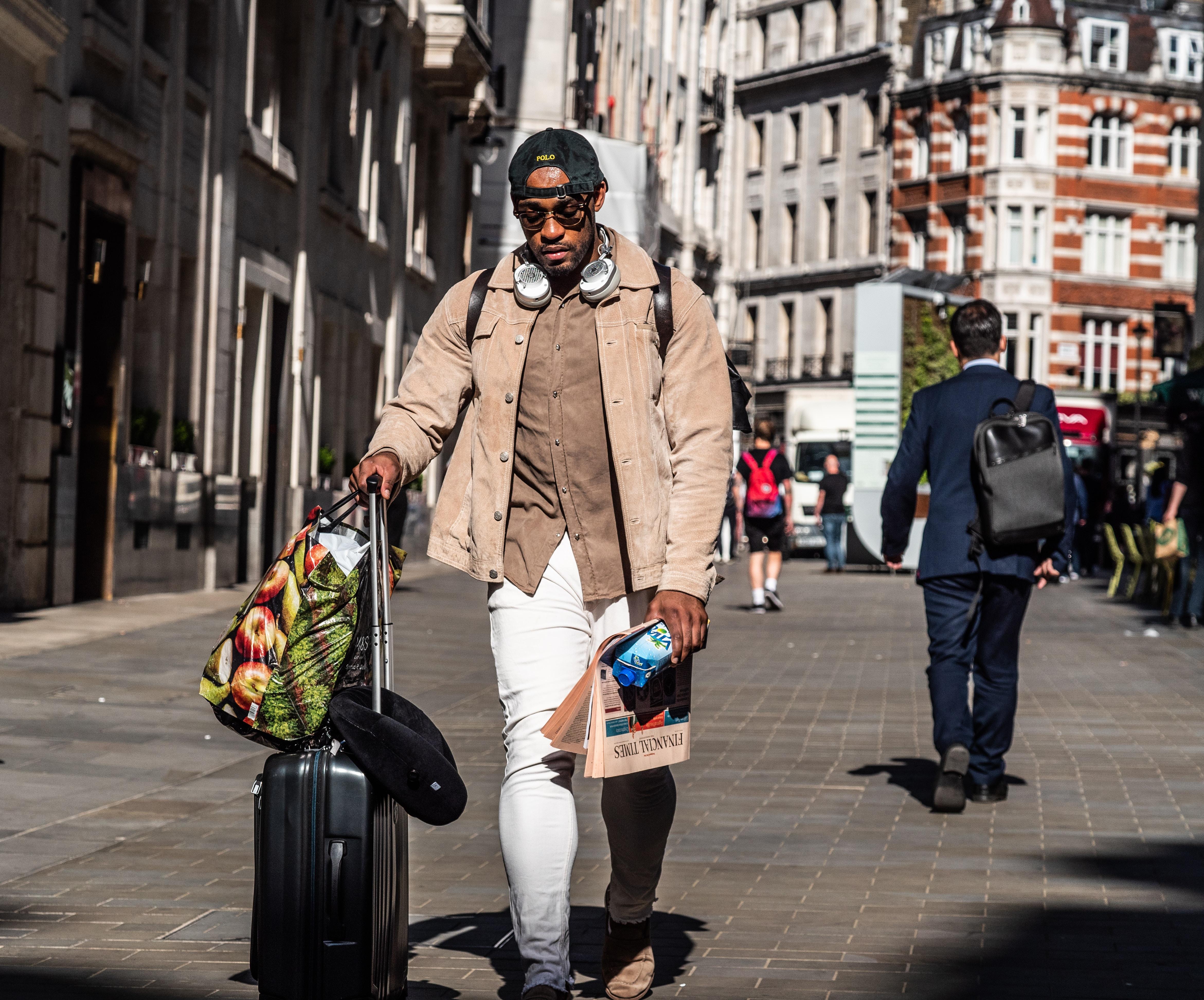man wearing brown shirt pulling black luggage