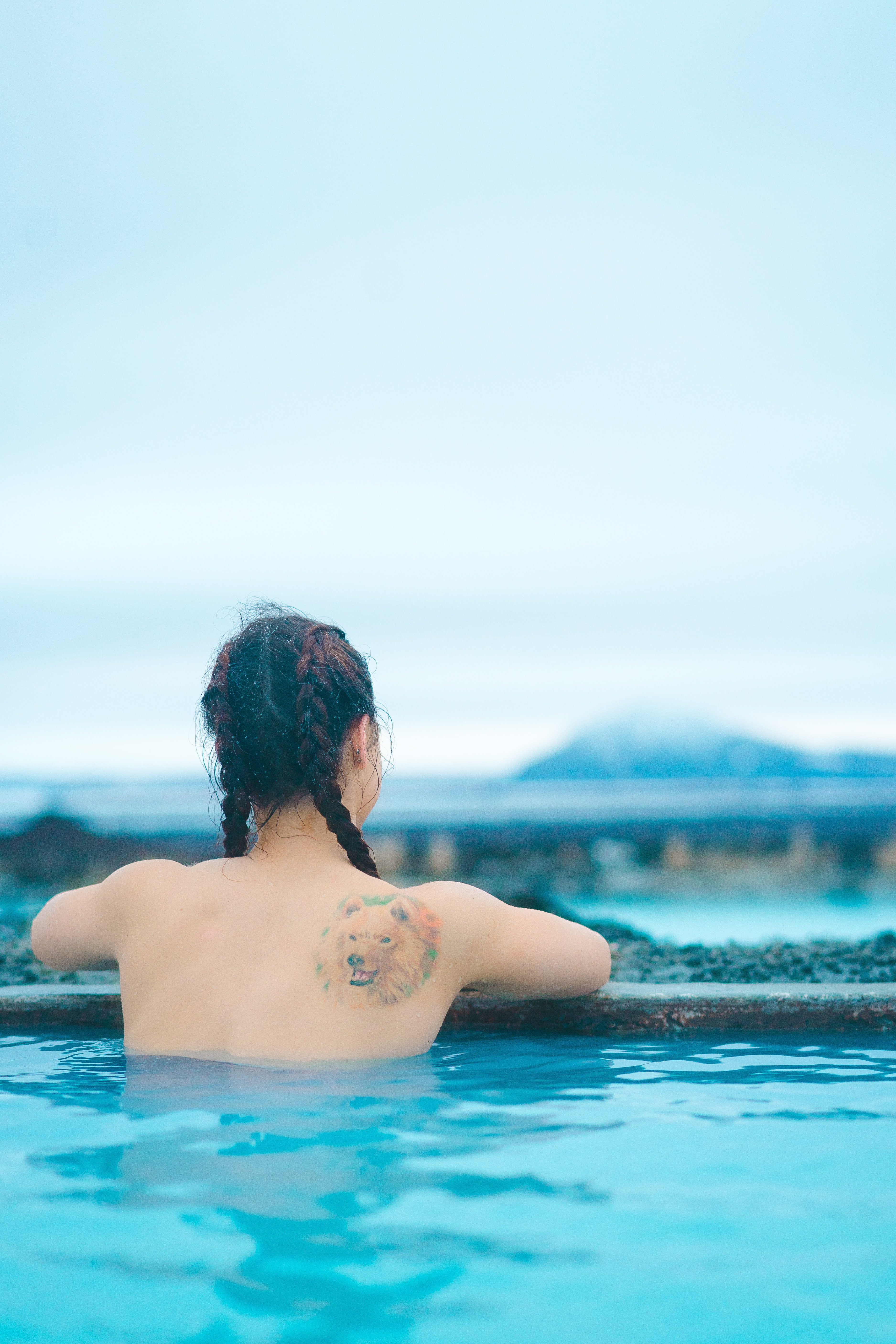 topless woman with wolf tattoo on the body of water