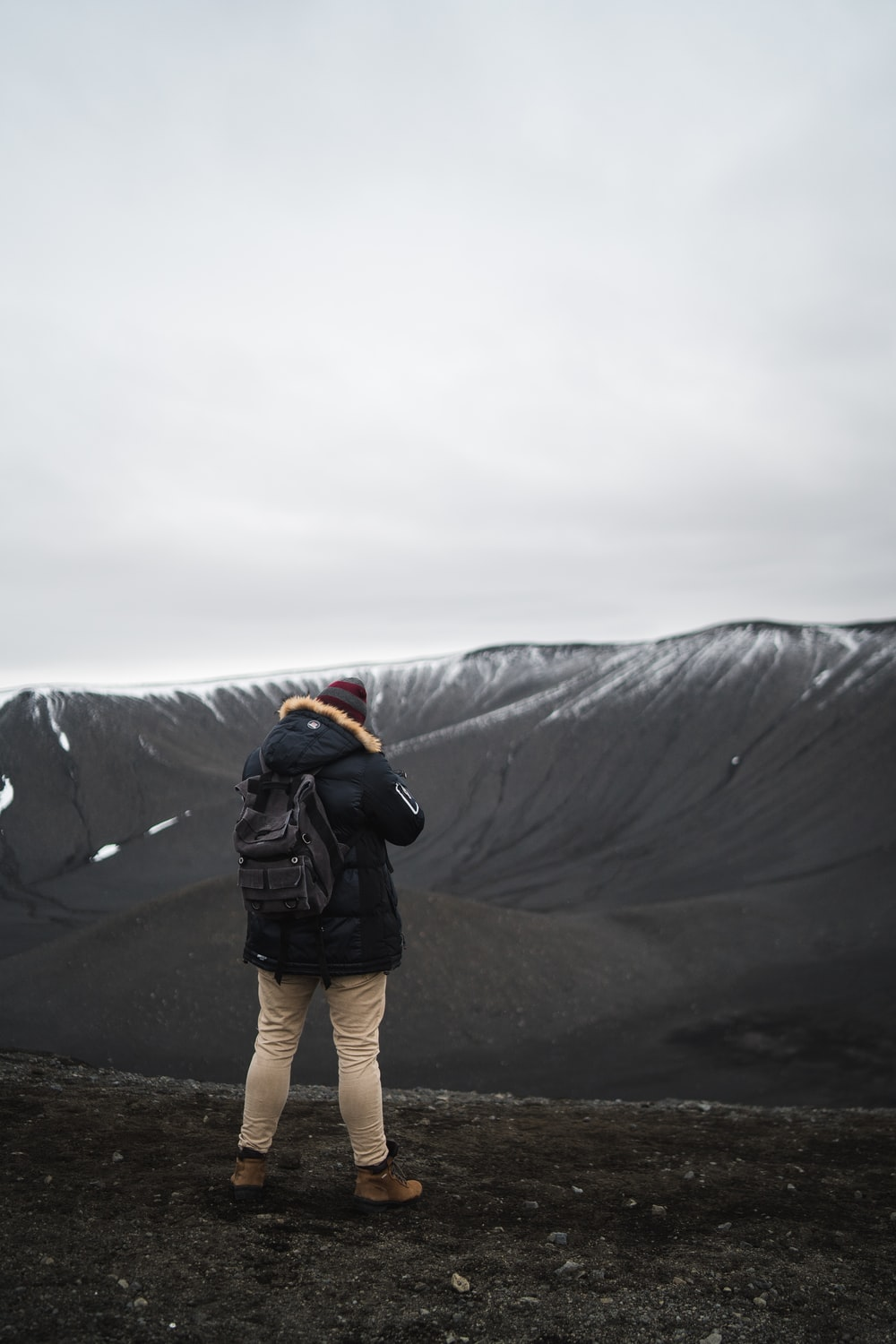 person in black parka jacket standing on brown soil