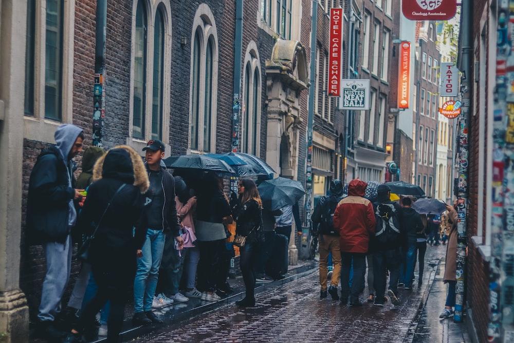 group of people on sidewalk with umbrella