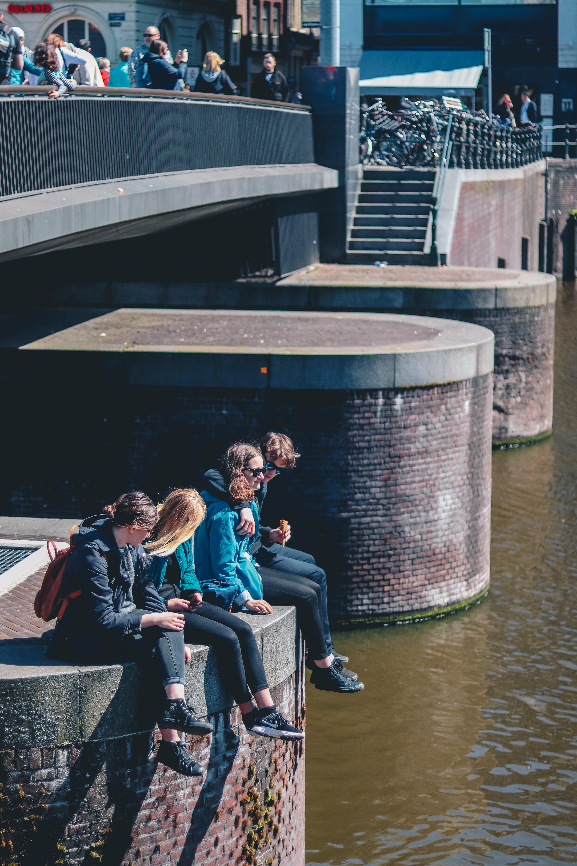 four people sitting near bridge