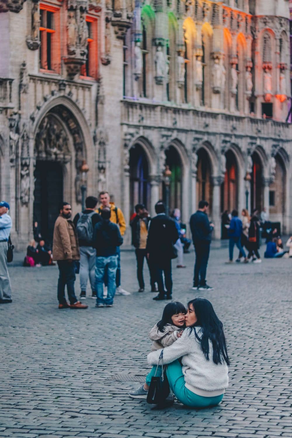 woman kissing girl while sitting near building