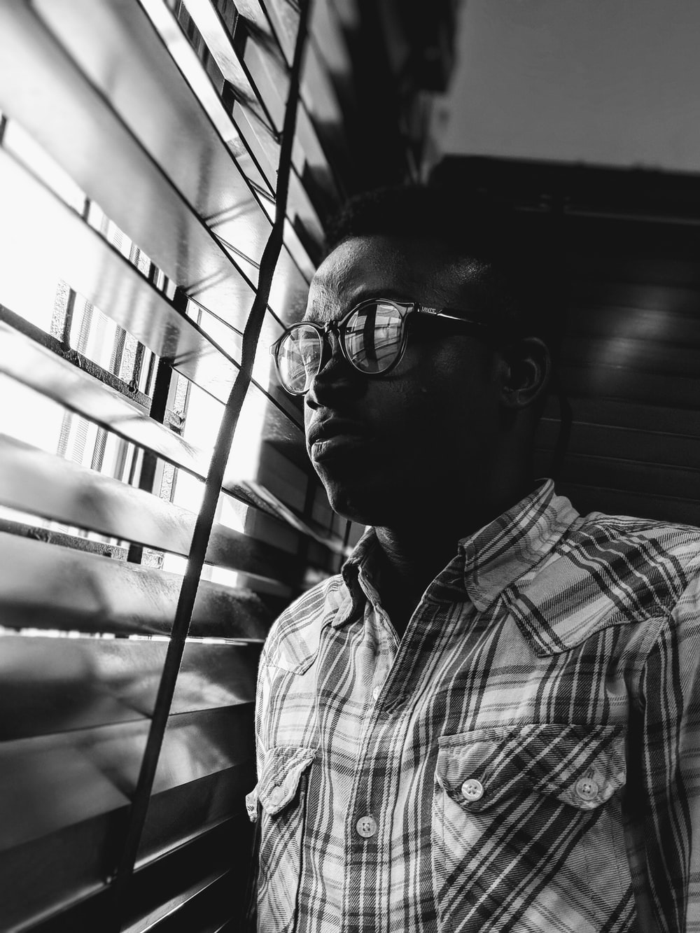 grayscale photo of man near window