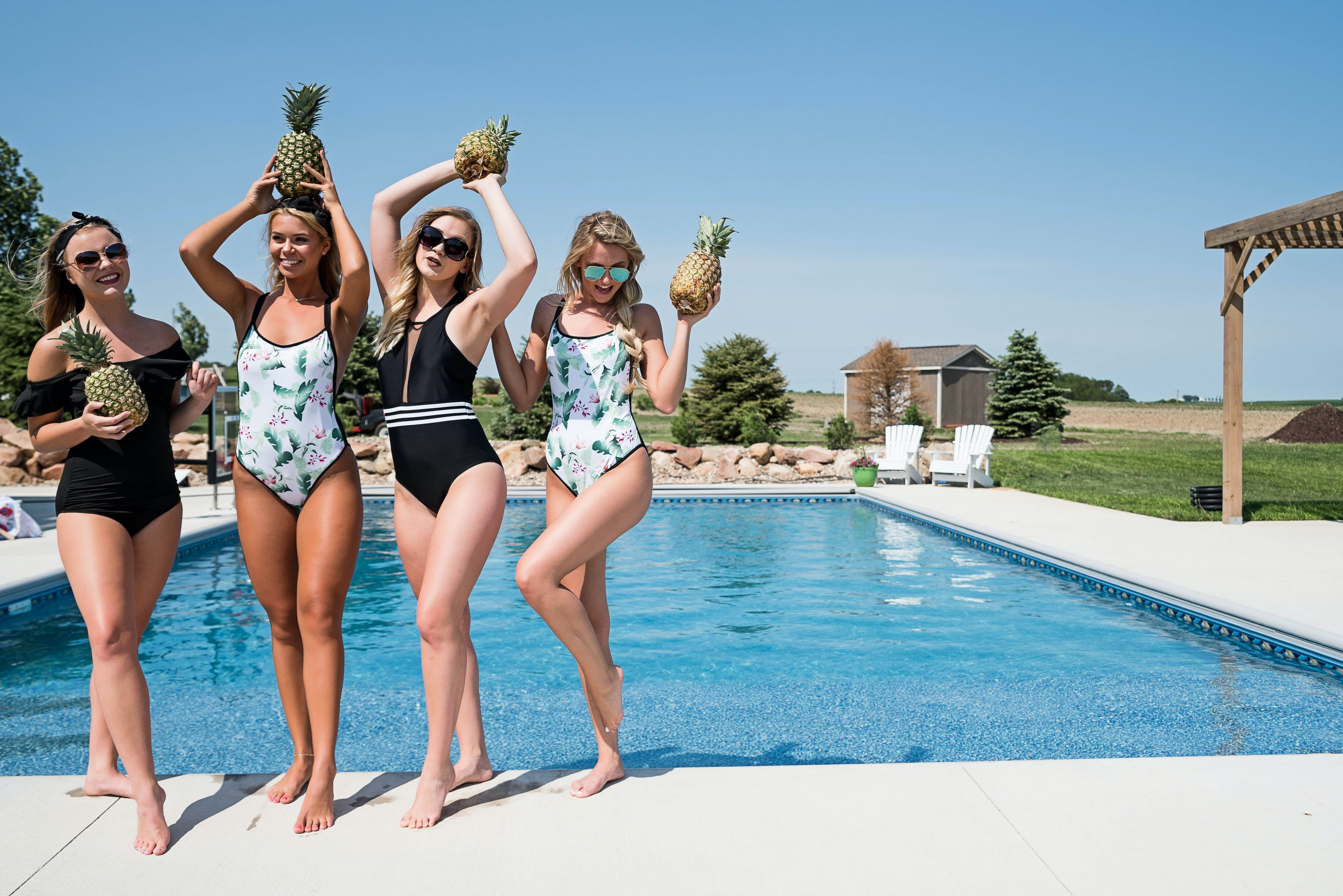 four woman standing near swimming pool